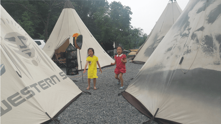Two young native american girls playing near tipis