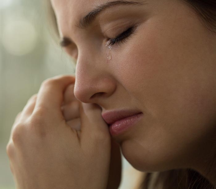Woman crying with hands touching face