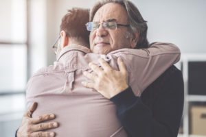 adult son hugging father