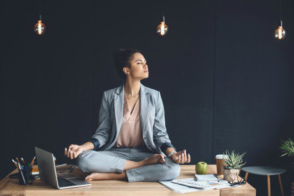 Meditating woman on office desk